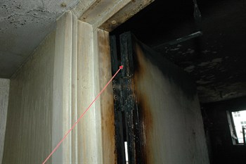 Intumescing strip on bedroom door has expanded due to hot fire gases and has helped to prevent smoke spread throughout the property.